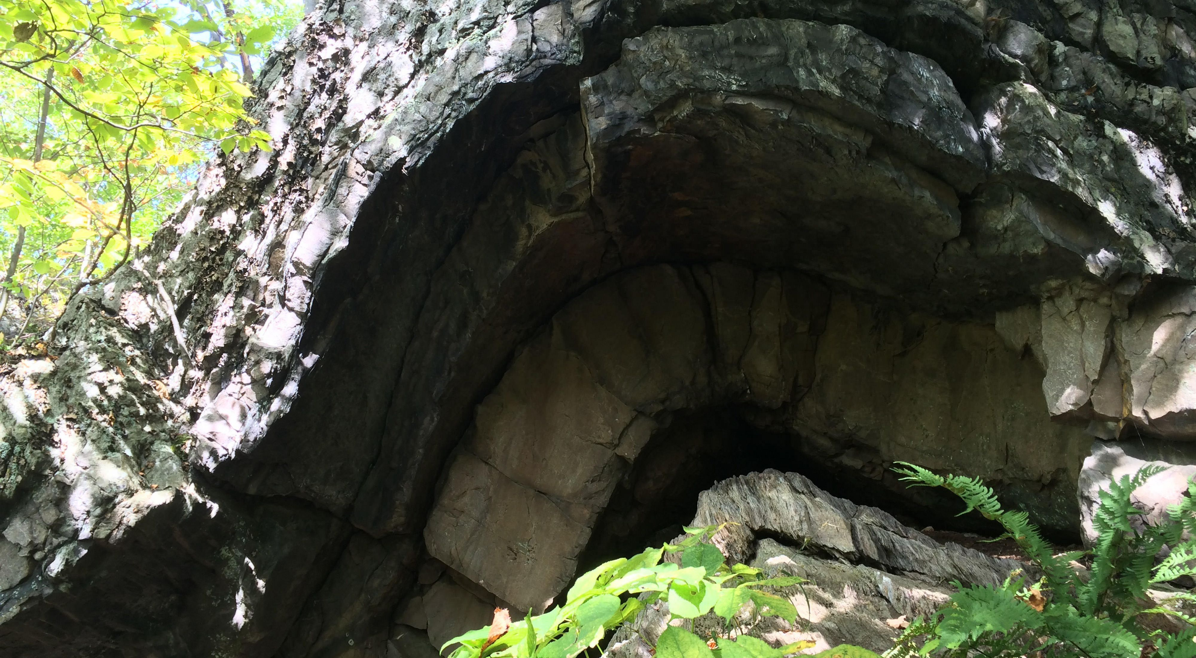 An arched rock formation leading into a cave under the arch.