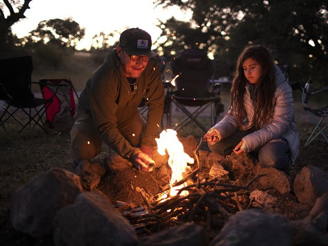 Older man and young woman sit next to small campfire roasting marshmallows.