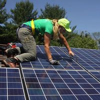Photo of a solar energy installer working on a solar panel with green trees in the background.