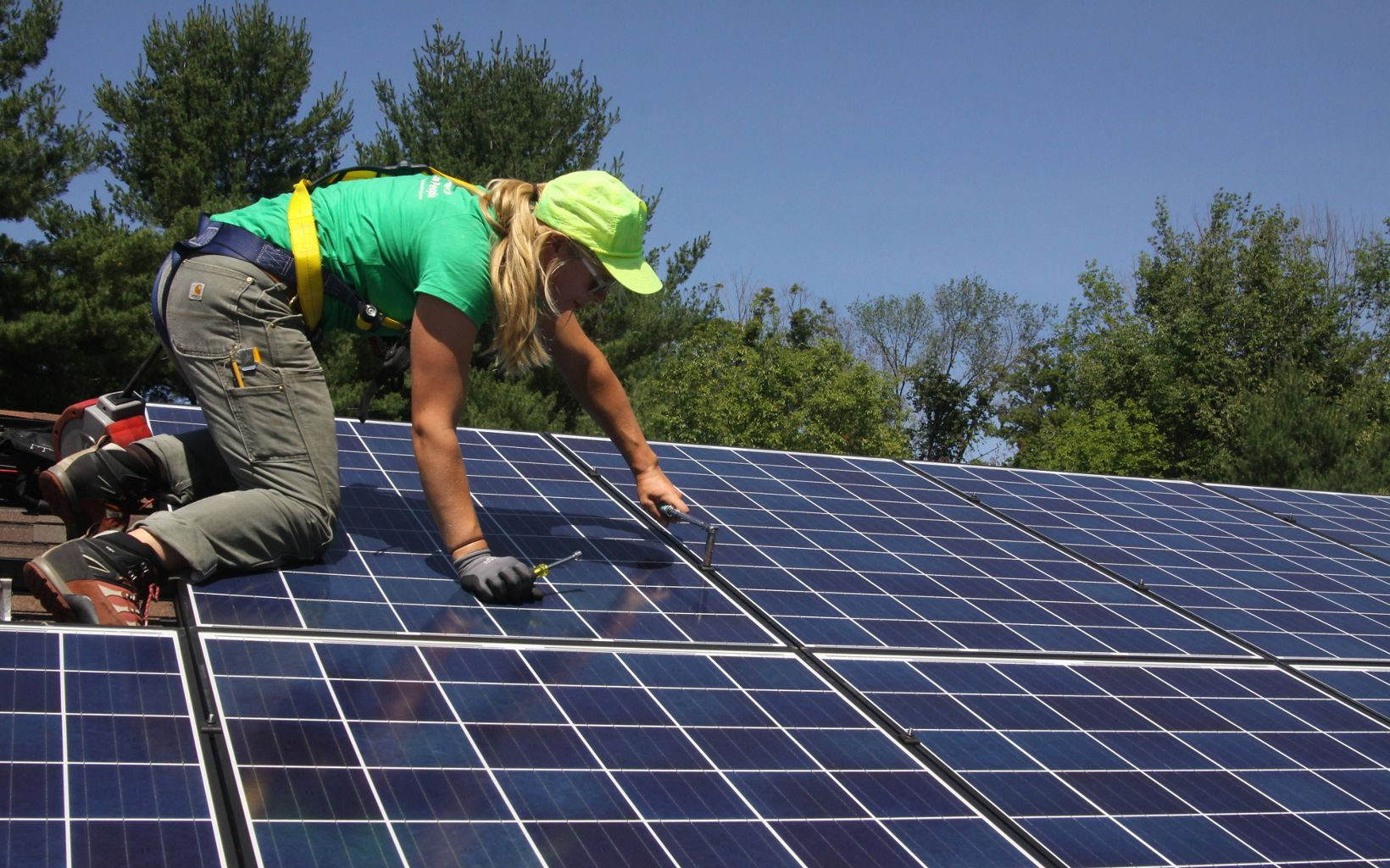 A worker kneels on a roof installing solar panels.
