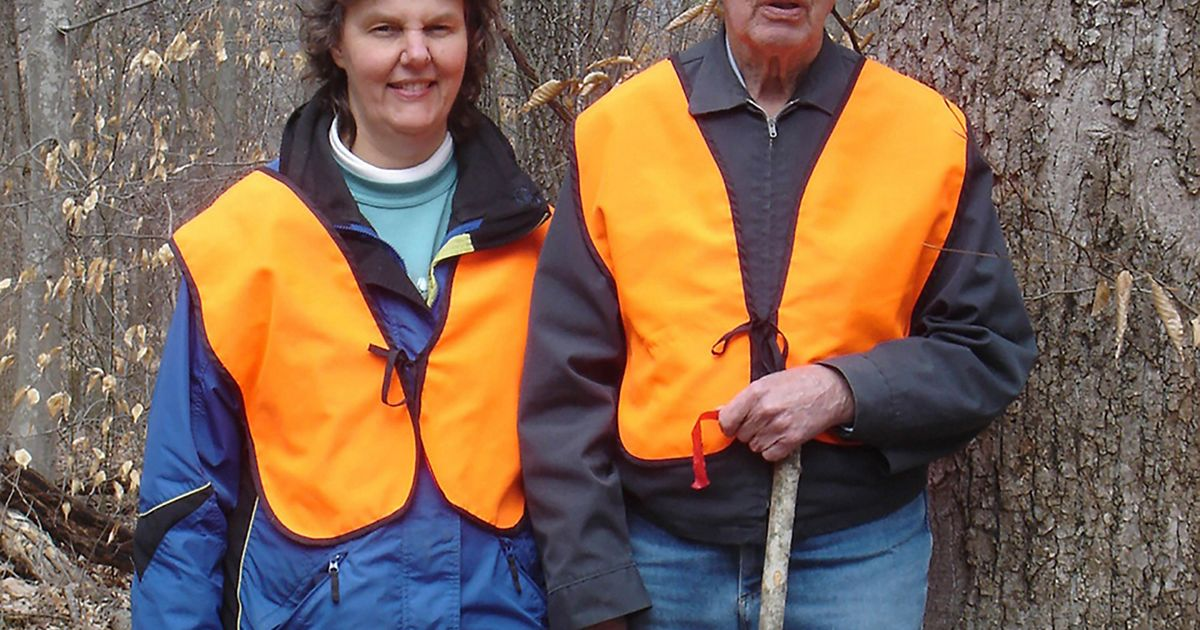 A father and daughter wearing orange vests pose next to a tree.