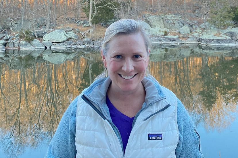 Candid headshot of Donor Relations Manager Rebecca Luib. A smiling woman wearing a winter parka stands in front of a pond. The water reflects the orange autumn color of the trees behind her.