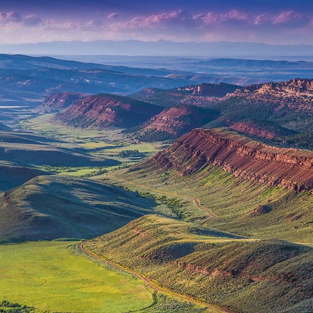 Aerial view of Red Canyon Ranch with verdant green slopes and red rock ridges.