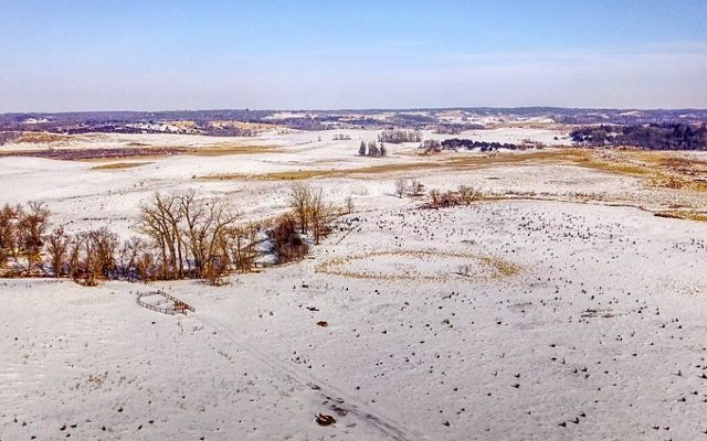 Aerial shot of grassland pastures covered in a thin layer of snow.