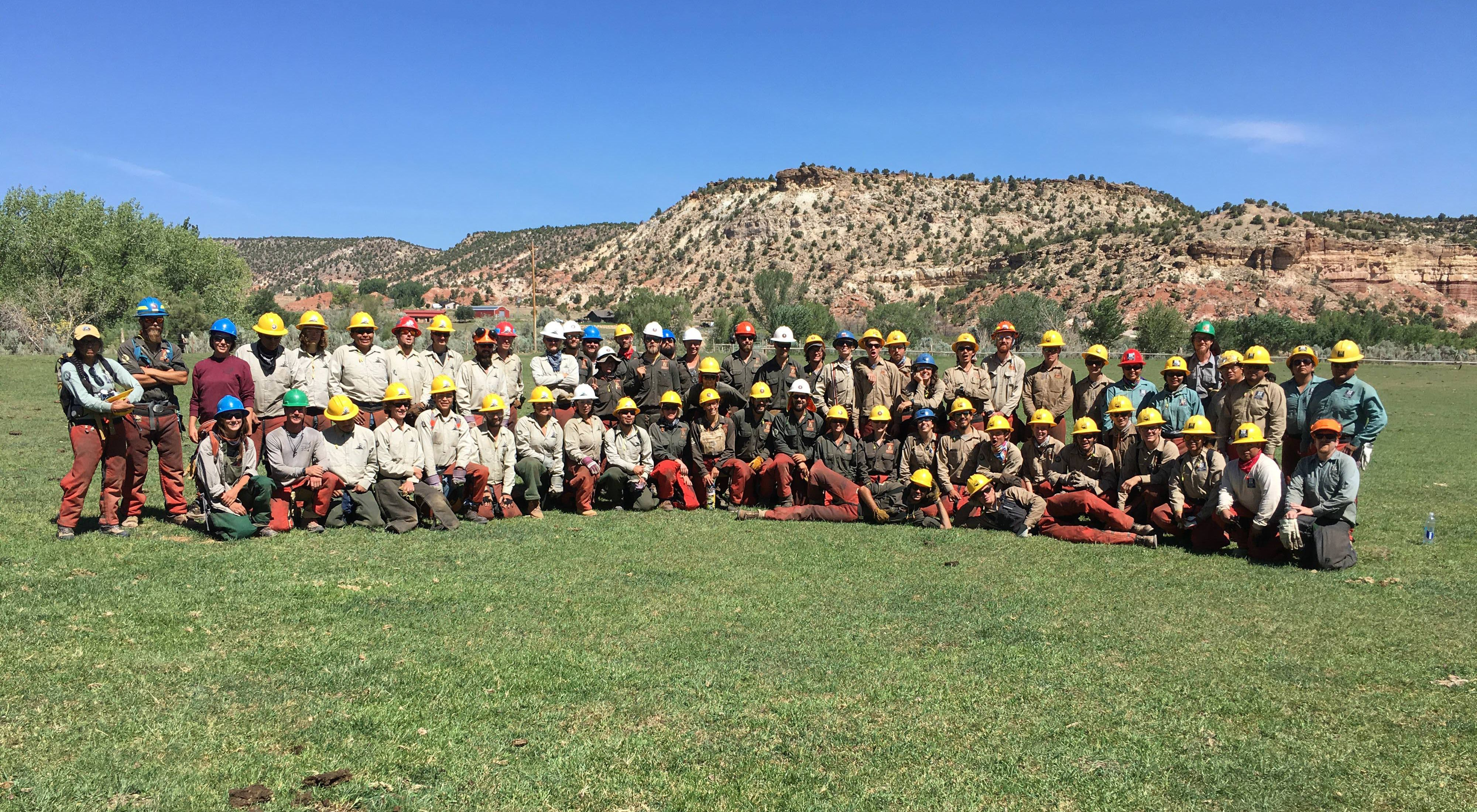 A group of more than 50 restoration crew members pose in rows, standing and sitting in the grass with red rock outcrops in the background.