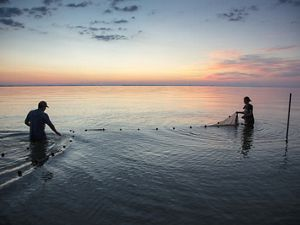 Two people stand apart, waist-deep in calm waters, holding an outstretched net between them as the sun sets behind them.