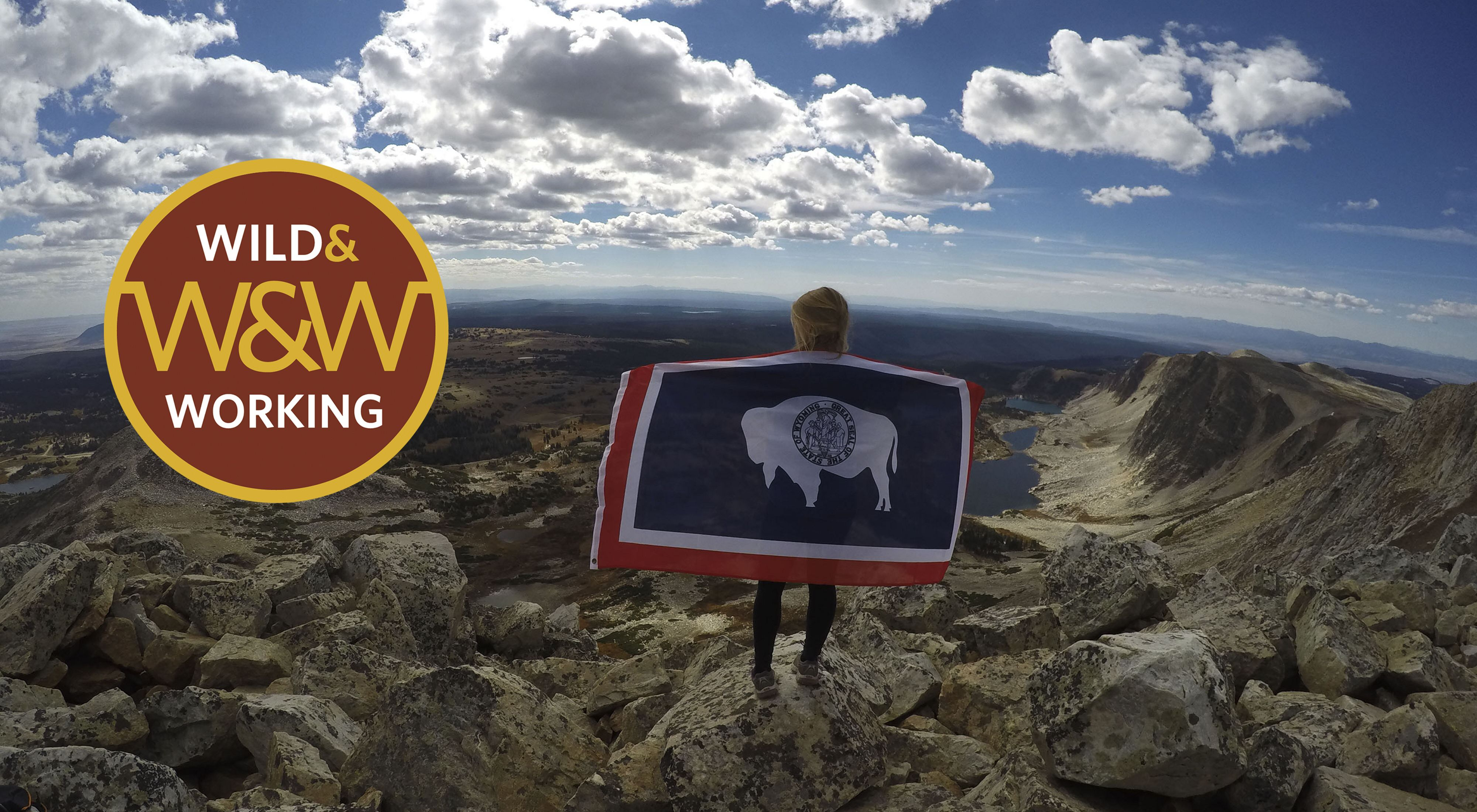 Girl with Wyoming state flag stands on mountain under cloudy blue skies.