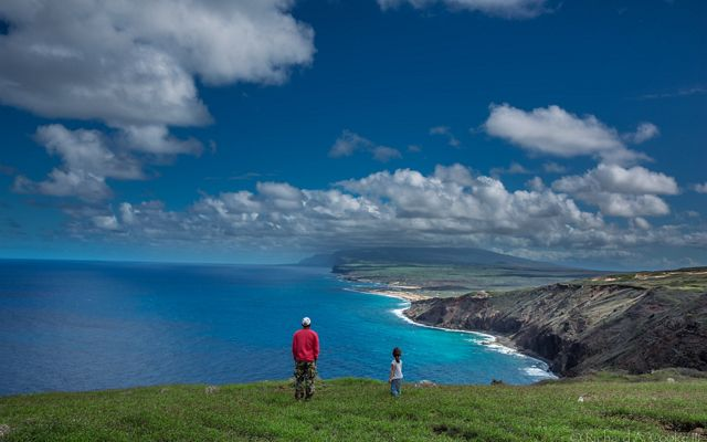 two people looking over a scenic ocean vista