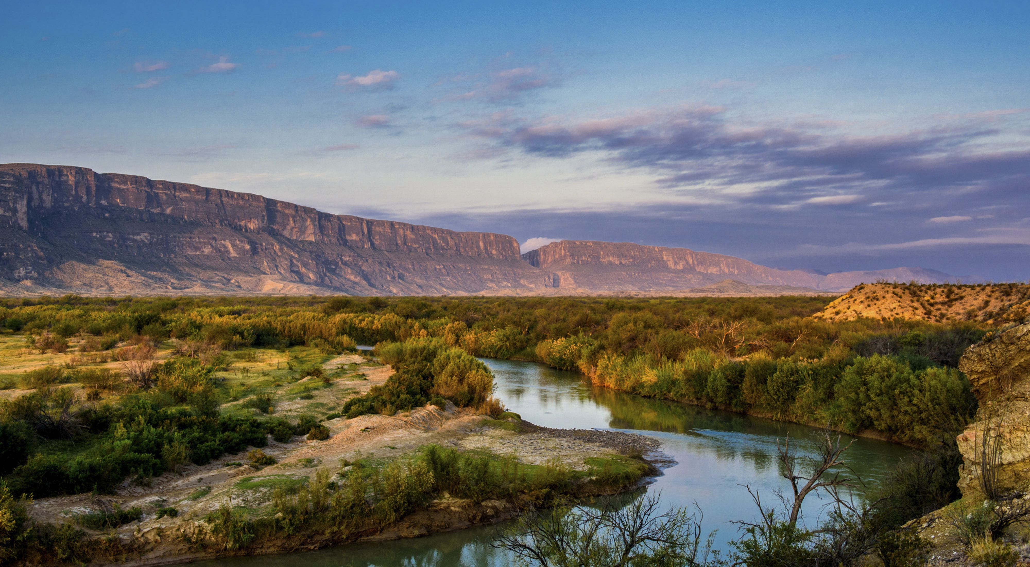 a view of the rio grande and a canyon in the background against a sunset sky