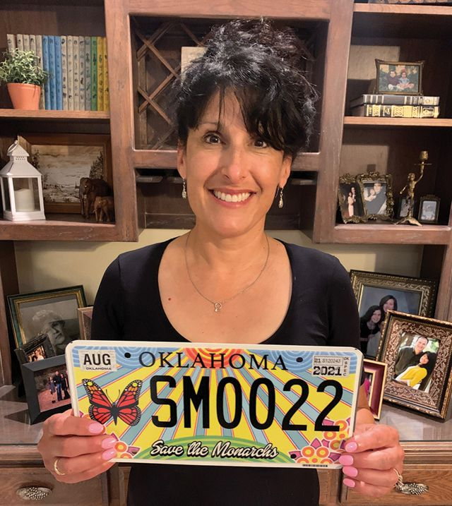 Woman holding monarch themed license plate.