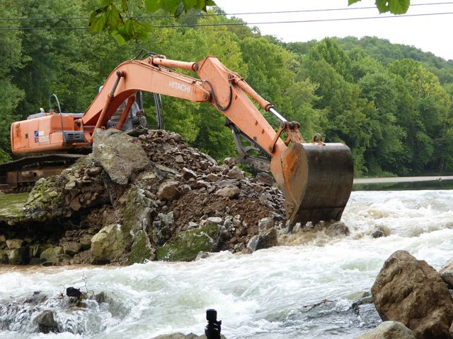 A large digger that has pushed concrete and earth from a fam aside to allow water to rush past.