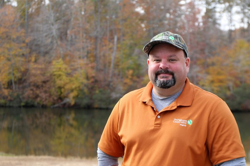 A man poses for a photo standing outside in front of a lake. He is wearing an orange sport shirt. The trees are reflected in the surface of the water behind him.