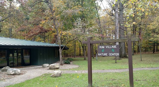 One-story nature center sits among trees in autumn.