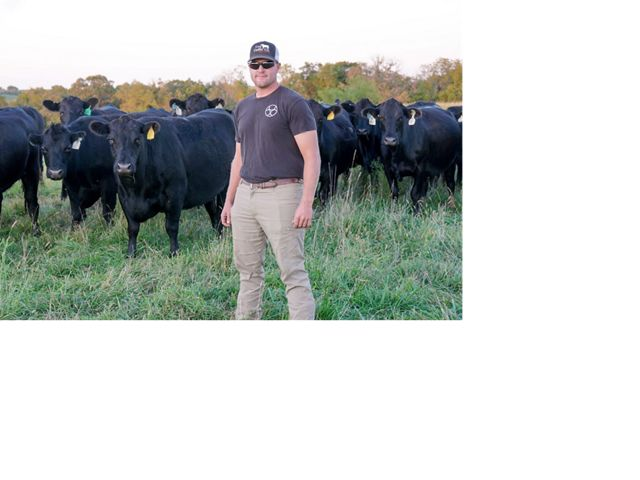 Ryan Cox stand with his cattle on Little Creek Farm.