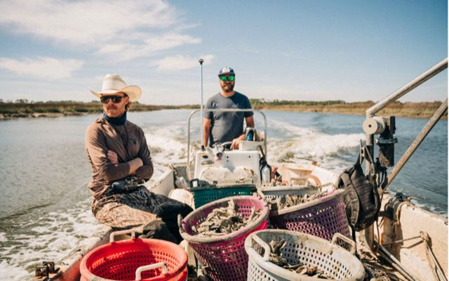 Two oystermen on a boat filled with oyster cages, on the water.