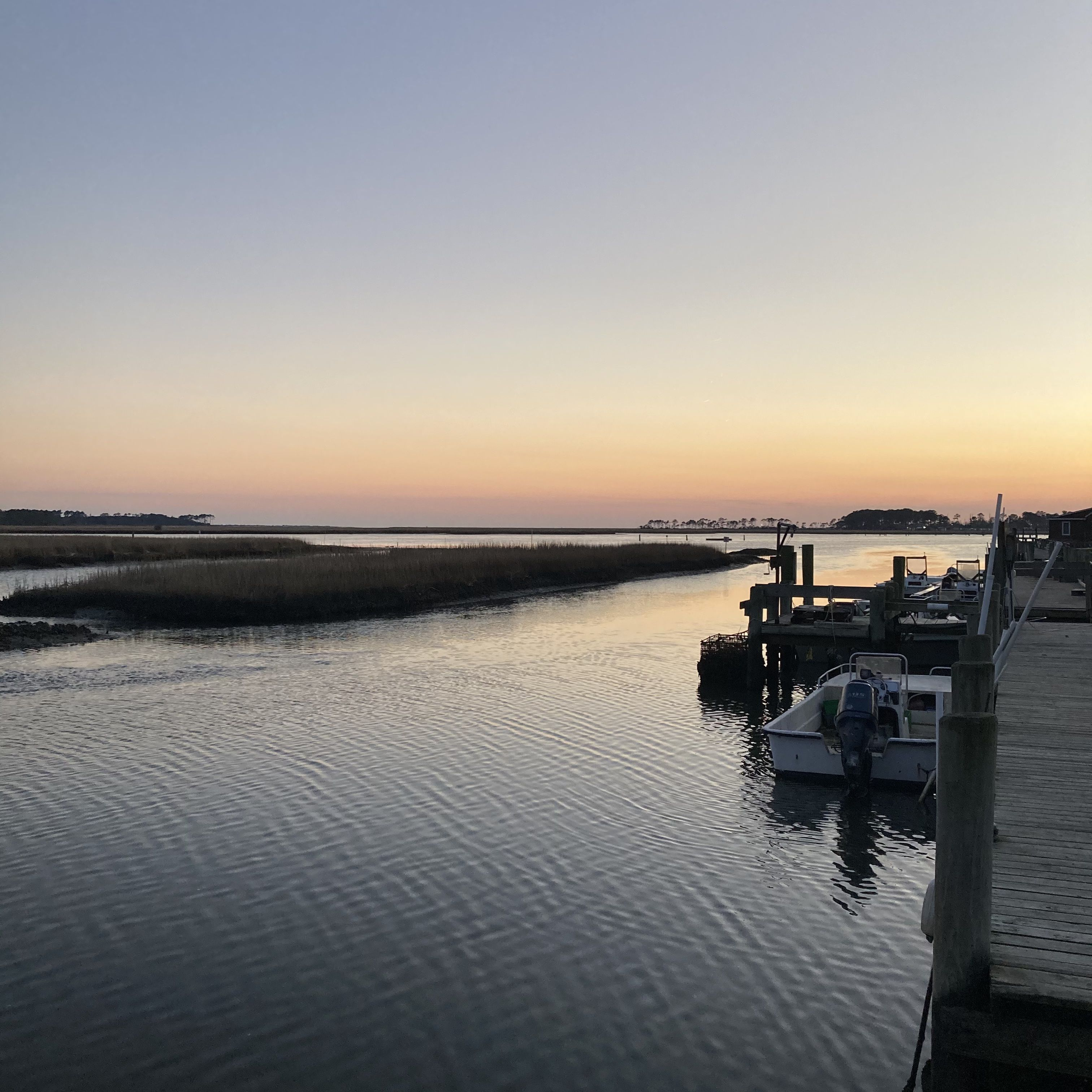 Sunset over the pier and water on an oyster farm.