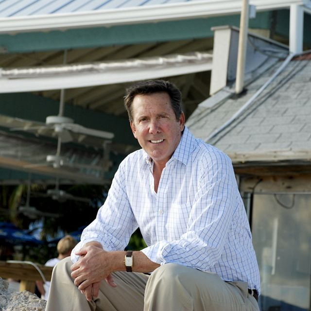 A smiling man sitting in front of a seafood restaurant.