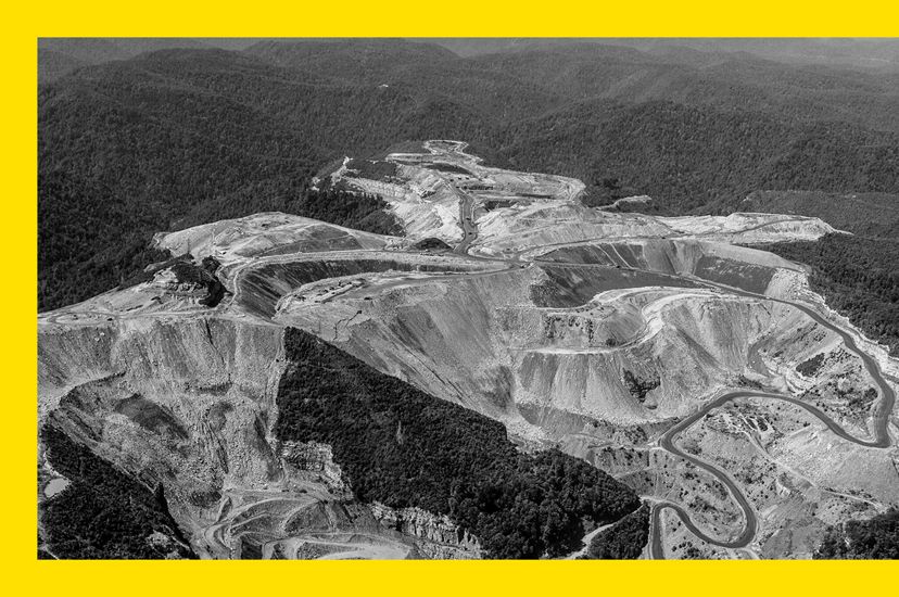 Black and white aerial photo of a mountaintop coal mine in West Virginia, showing degraded land surrounded by forest.