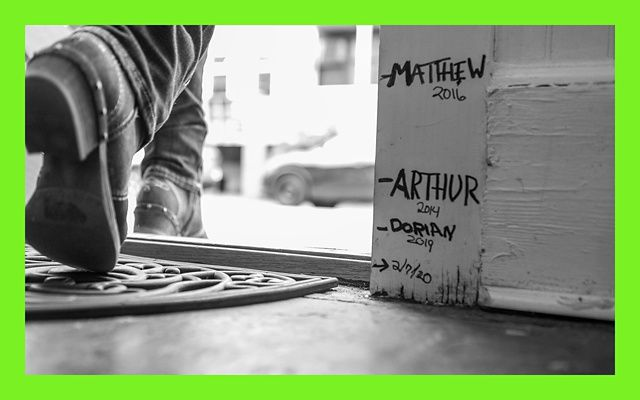 Black and white photo of a doorway with multiple hurricane flood levels marked: Matthew 2016, Arthur 2014, Dorian 2019.