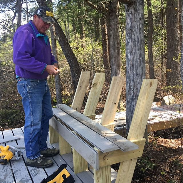 A volunteer helps build a new viewing platform and bench at Saco Heath preserve.