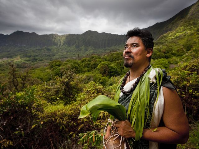 Man in dressed in Hawaiian cultural clothing, mountains in the background.