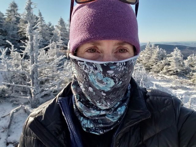 Samantha Horn closeup shows frost and snow covered, stunted trees and distant mountains behind her.