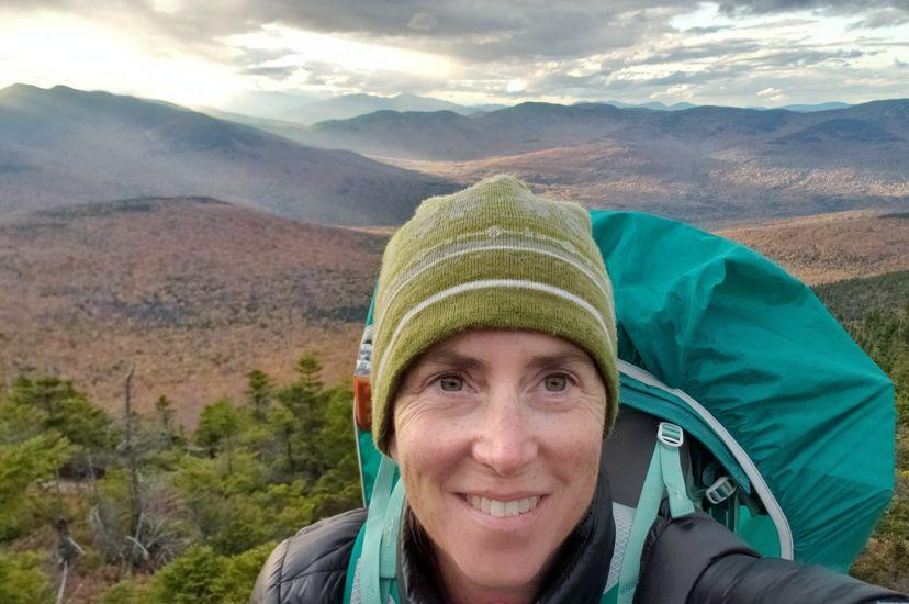 Samantha Horn se toma un retrato frente a un paisaje montañoso.