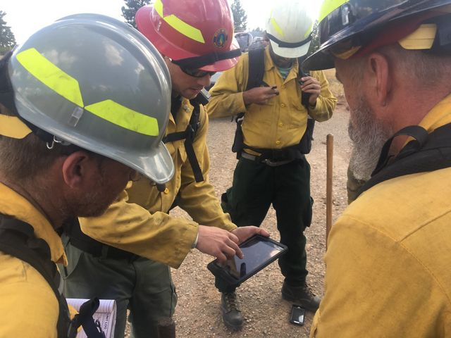 A closeup of four participants of a fire training exchange viewing a digital map of a burn unit.