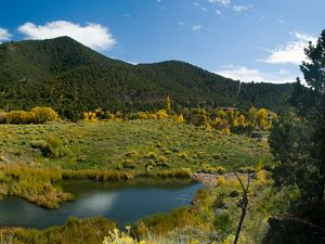 River runs through brush country with mountain in background.