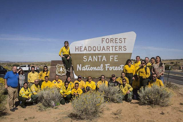 Participants of a Spanish-language fire training exchange pose in front of a sign for the Santa Fe National Forest.