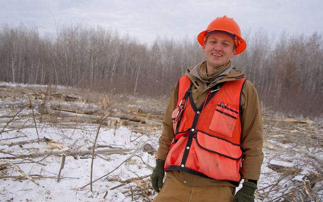 A smiling forester wearing an orange vest and hardhat.