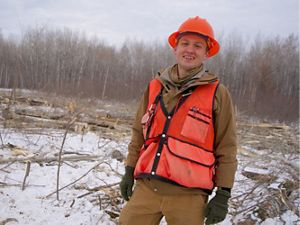 A smiling forester in an orange hard hat.