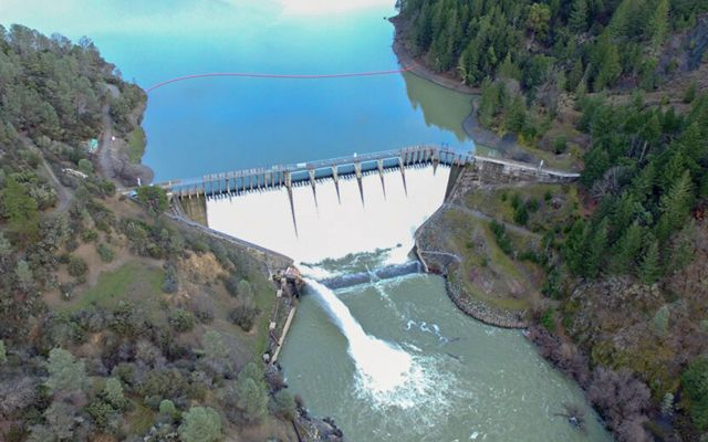 Aerial view of Scott Dam at Lake Pilsberry, a large dam with a high flow of water coming over and through it.
