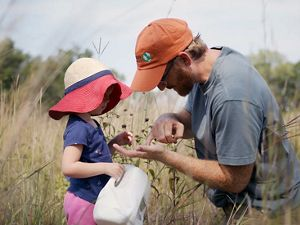 A father shows a child seeds he has collected in a field.