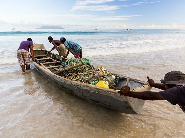 Fishermen in the Seychelles push a boat into the water