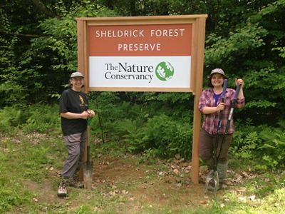 Two people standing in front of a sign that says Sheldrick Forest Preserve.