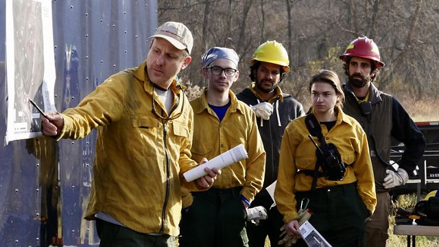 A man wearing yellow protective fire gear points to a map hung on a wall during a briefing for a controlled burn.