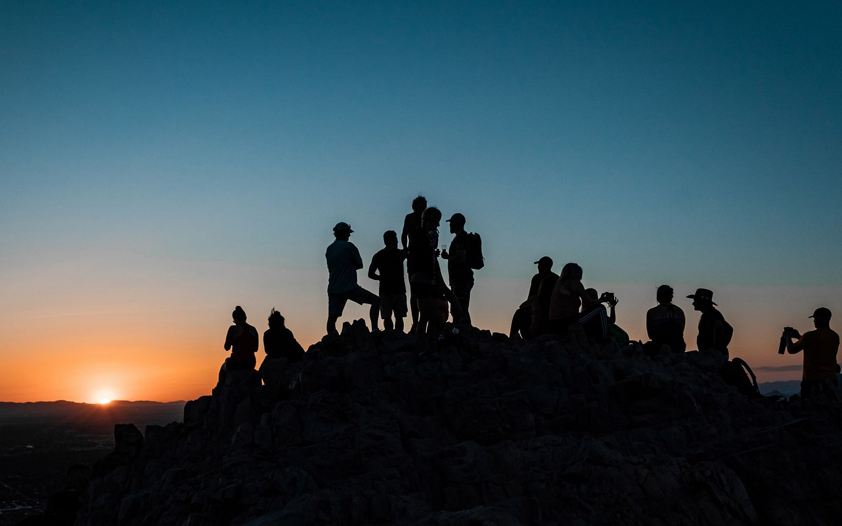 Several groups of people on a hillside silhouetted against a dark blue sky with an orange-pink sun setting on the lefthand side of the field of view.