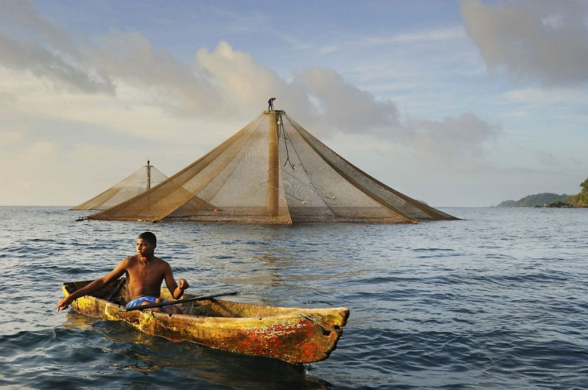 a fisher sits in a small boat on open water with two tents rising above the water behind him