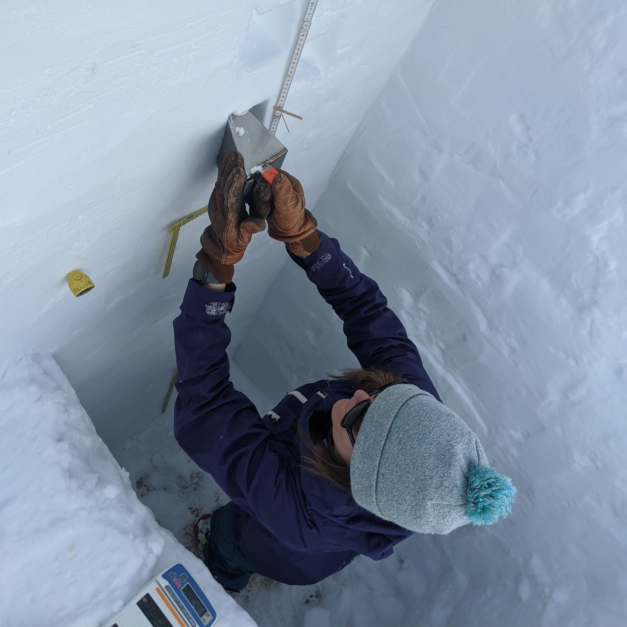 A woman in cold weather gear measures snow in a large square hole.