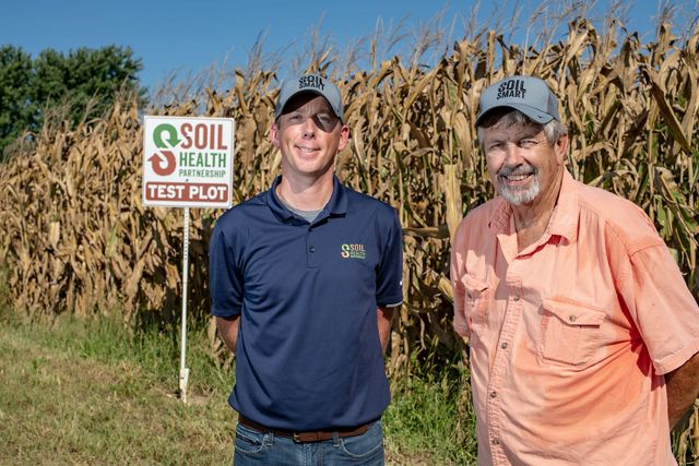 Two men with hats stand beside rows of corn, a sign near them for the Soil Health Partnership test plot.