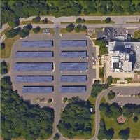 Aerial view of a 5 rows of solar arrays surrounded by trees with a building in the center.
