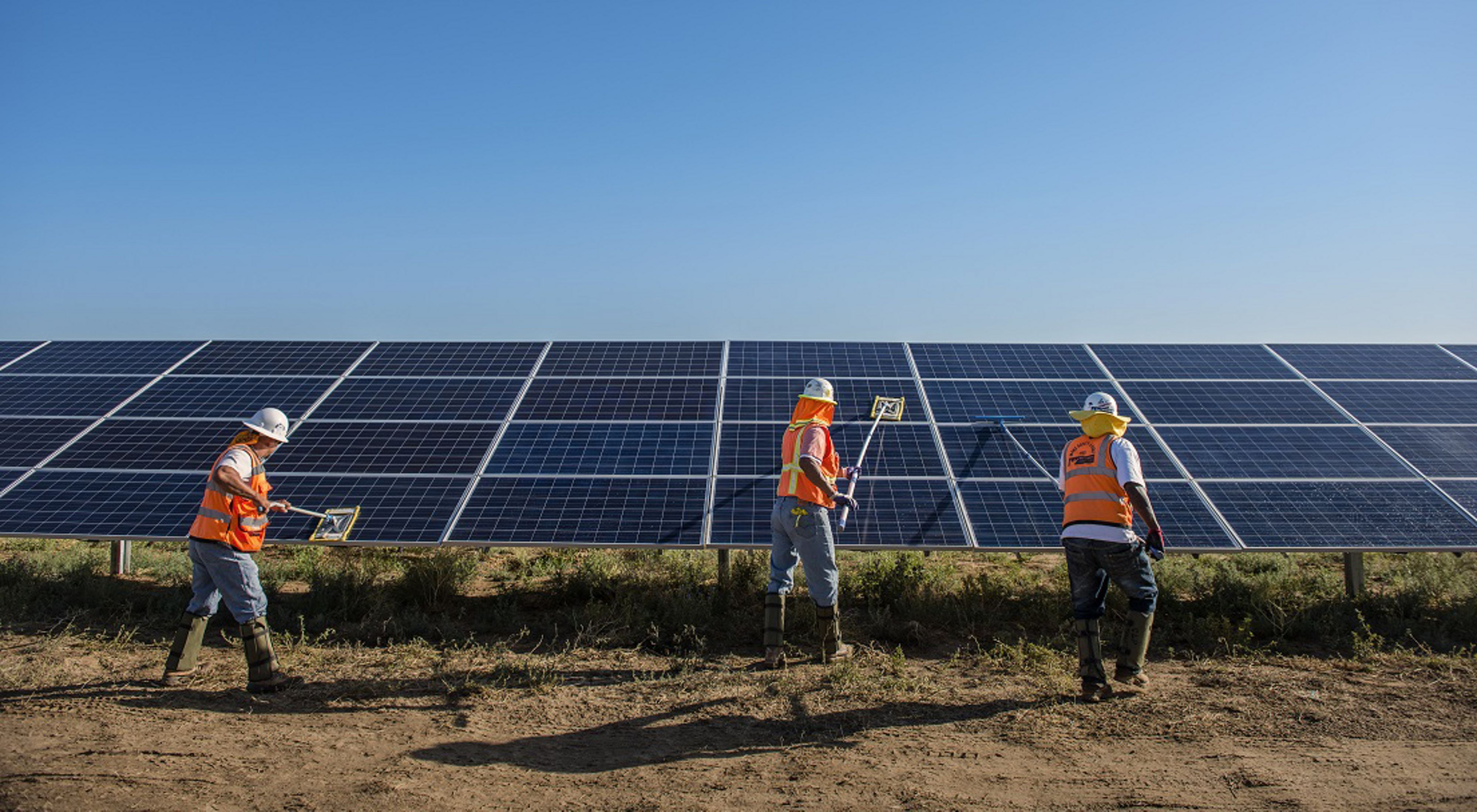Three workers in hard hats cleaning solar panels