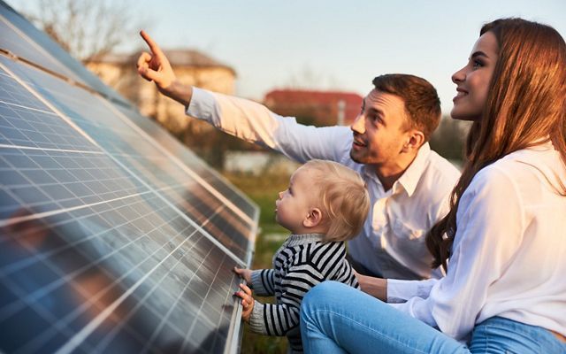 Man shows his family the solar panels on the plot near the house during a warm day. Young woman with a kid and a man in the sun rays look at the solar panels.