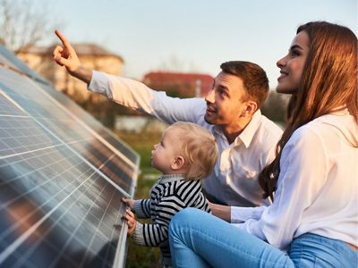 A man, woman and child look at a solar panel.