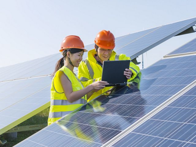 One male and one female engineer are using notebook and discussing at the solar panel.