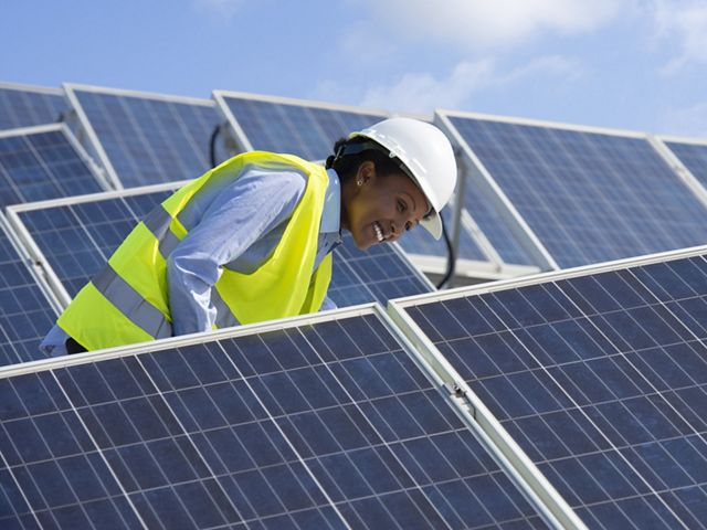 A worker in a hard hat stands between rows of solar panels.