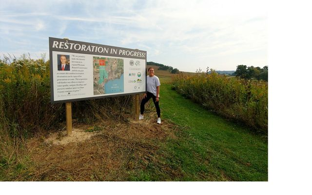 Sophie Meringoff stands by sign that says Restoration in Progress, which highlights her family's donation to the project