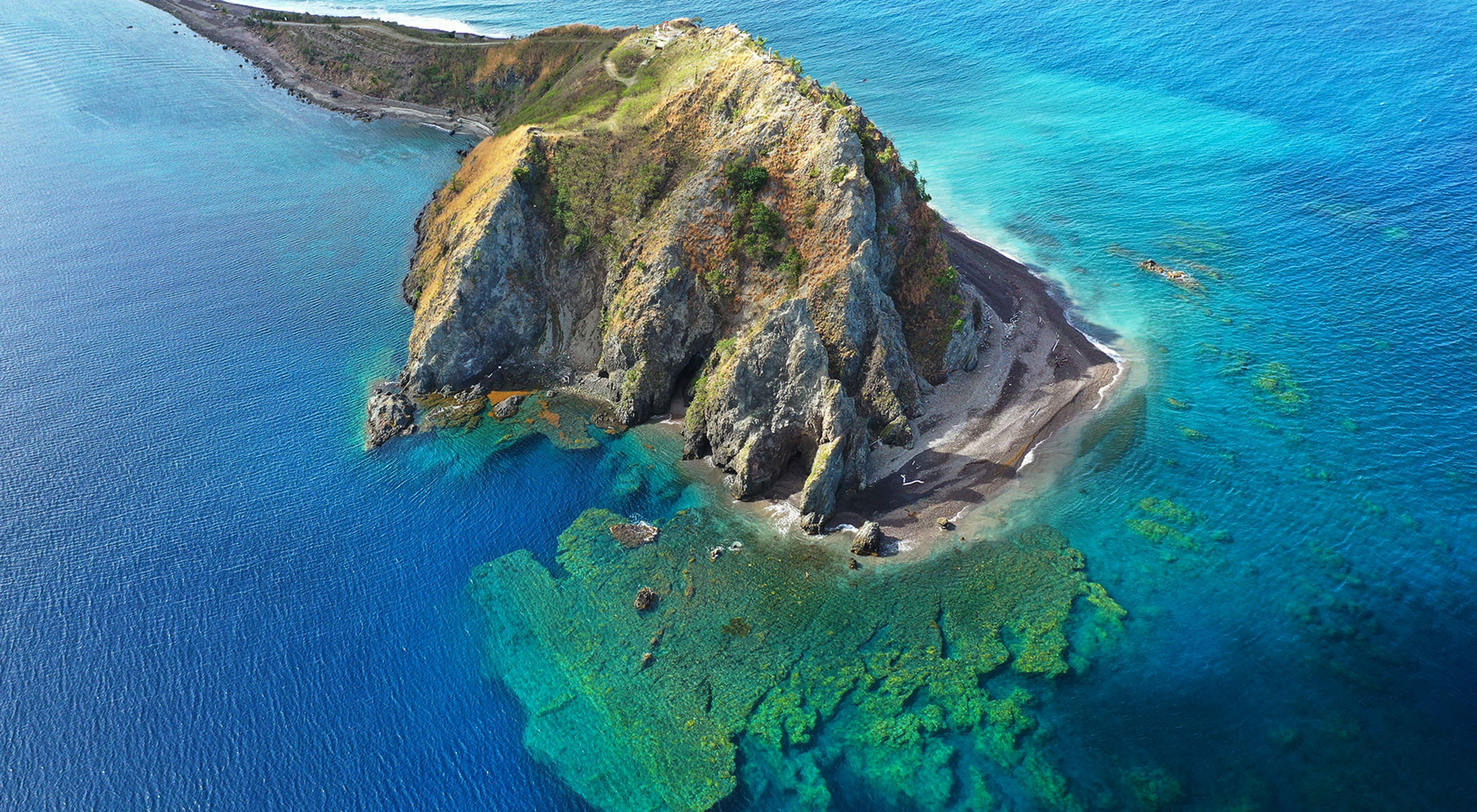 Aerial view of coastal cliffs and coral reefs below water's surface in Soufriere-Scott's Head Marine Reserve in Dominica.