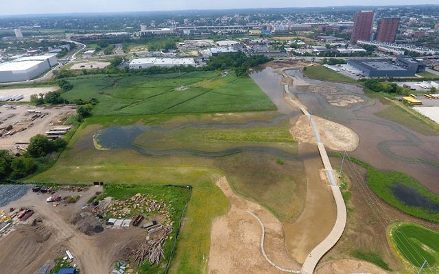 Aerial view looking down on the construction site of a large urban park. A wide boardwalk winds through the center of an open wetland area.